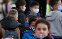 A group of young students are shown wearing face masks and back packs as they wait in liine.