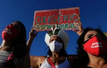"""Demonstrators wearing masks with text written in Portuguese that read """"Bolsonaro out,"""" and a sign with the phrase """"Oxygen, Breathe Brazil,"""" protest against the government's response in combating COVID-19 and demanding the impeachment of Brazil's President"""