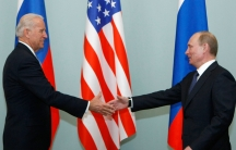 Joe Biden is shown with his hand outstretched shaking the hand of Vladimir Putin.