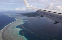 A plane flies over blue ocean waters and small island strips.