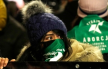 A crowd of people are shown with a woman in the center holding a banner and wearing a winter hat and green scarf with writing on it.