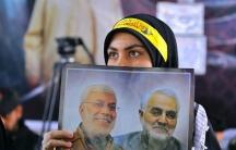 A woman holds a poster showing Gen.Qasem Soleimani, right, head of Iran's Quds force and Abu Mahdi al-Muhandis, deputy commander of the Popular Mobilization Forces, during the procession to commemorate the first anniversary of their killing by a US drone