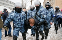 Several police officers are shown wearing winter camoflage and helmets while carrying a man by his arms and legs.