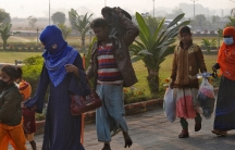 Four people walk with their belongings outside. A woman wears a blue scarf on her hair. A barefoot man carries a bag on his shoulder.