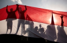 The dark silhouetted of several people are shown with their hands in the air holding up the red, white and black-stripped Yemen flag.