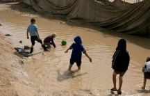 Children play in a mud puddle in the section for foreign families at Al-Hol camp in Hasakeh province, Syria onMarch 31, 2019.