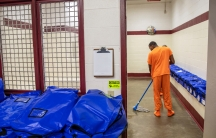 An inmate wearing an orange suit mops near blue plastic bags inside a detention center.