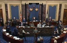 A photo taken from a video above the US Senate chamber showing lawmakers, two rounded wooded tables and the dais.