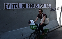 """A man rides a bike by a slogan pasted on a wall reading """"Avoid a rape trial: Become chief of police,""""in Paris, Saturday, July 11, 2020."""