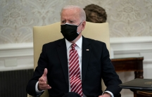President Joe Biden wearing a dark suit and red and white tie along with a face mask while sitting.