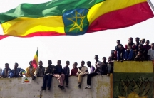 A huge flag of Ethiopia waves with people sitting underneath it