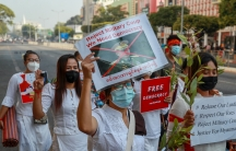A demonstrator displays a picture of the defaced image of the commander in chief, Senior Gen.Min Aung Hlaing, also chairman of the State Administrative Council to protest against the military coup in Yangon, Myanmar, Feb. 17, 2021. The UNexpert on human