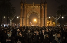 Demonstrators march near the Arch of Triumph during a protest condemning the arrest of rap artist Pablo Hasél in Barcelona, Feb. 22, 2021.