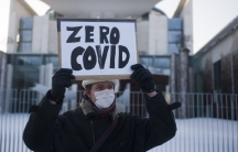 """A man holds a sign that says """"zero COVID"""" wearing a winter jacket and hat outside in front of chancellery in Berlin."""