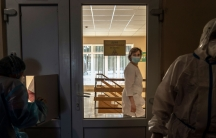 A nurse is shown through the glass of a closed door looking into a darkened room with two other medical professionals dressed in protective clothing.