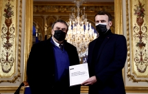French President Emmanuel Macron is shown standing next to French historian Benjamin Stora, both men wearing dark jackets and Macron holding a white paper.
