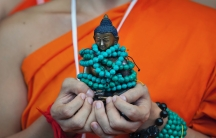 A Thai Buddhist monk carries a statue of Buddha as he waits with others to welcome Tibetan spiritual leader Dalai Lama at the Tsuglagkhang temple in Dharmsala, India, Sept. 7, 2018.