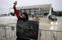 """A demonstrator wearing a mask against the spread of the new coronavirus holds a sign that reads in Portuguese """"Justice for Lula,"""" in reference to former Brazilian President Luiz Inácio Lula da Silva, during a protest commemorating the Supreme Court's deci"""