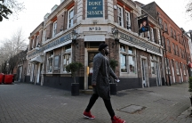 A man is shown with white headphones and read shoes walking past a pub called The Duke of Susex.