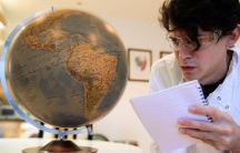A man wearing glasses looks at a globe.