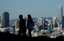 The downtown skyline of San Francisco is shown in the distance with a couple walking in the nearground in shadown.