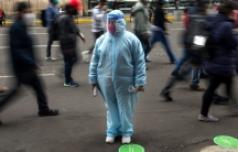A woman is shown standing and wearing a full blue medical protective outfit with several people walking past her in blurred motion.