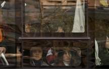 Women look out of a crowded bus traveling from the outskirts of Beijing.