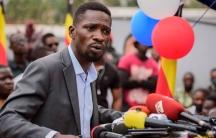 Ugandan opposition figure Bobi Wine is shown wearing a gray blazer an speaking into severla microphones.