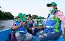Four people wearing blue jackets and green caps ride in a boat on a lake.