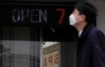 A man is shown in blurred focus walking past a digital sign that says, 'open 7' and glass beneth it with the sign for Gold Spa in the reflection.