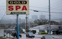 A sign above a roadway is shown for Gold Spa as cars pass by on a rainy afternoon.