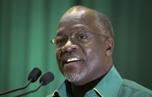 John Magufuli wears glasses a green shirt and speaks at a podium with a green background