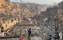 Several people are shown standing in the burned down ruins of the Balukhali refugee camp.