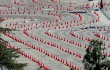 Several long lines of traffic cones are shown winding around an empty parking lot.