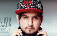Ali ATH, rapper wearing a red and black cap and holding headphones around his neck.