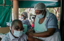 A man receives a shot from a health worker, both wear masks and protective gear.