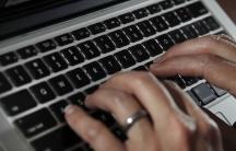 Fingers type on a laptop keyboard