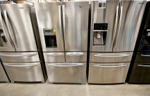 A selection of silver refrigerators on display at an appliance store.
