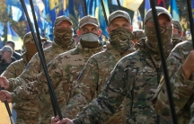 A line of men are shown wearing Ukrainian military fatigues and holding flag poles.