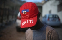 """A young migrant shows off his red """"Haiti"""" cap in Tijuana."""