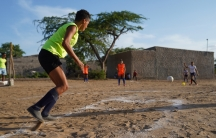 """Maria Isabel Parra takes her turn """"at bat"""" duringa kickball match in Riohacha, Colombia, March 26, 2021."""