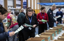 A small crowd of people are shown examining green ballots next to rows of boxes.