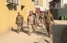 Group of US generals in army fatigues walk through the street in Afghanistan.