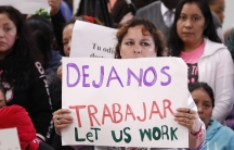 """An attendee at the House Homeland Security Committee field hearing at Tougaloo College in Jackson, Mississippi,holds a sign written in English and Spanish, stating """"Let us work,"""" Thursday, Nov. 7, 2019."""