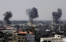 A city in the Gaza strip is show from afar with three clouds of black smoke rising.