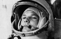 Soviet cosmonaut Major Yuri Gagarin is shown in a black and white portrait photograph wearing a space helmet with the visor open.
