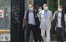 Hong Kong media tycoon Jimmy Lai, is shown wearing a light colored blazer with his hands handcuffed behind his back.