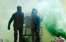 Two cemetery workers are shown pulling a casket on wheels with ceremonial green smoke surrounding them.