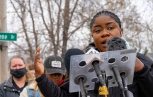 A woman speaks at a podium representing Black Immigrant Collective.