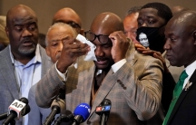 George Floyd's brother Philonise Floyd is shown lifting his dark-rimmed glasses up to wipes his eyes.